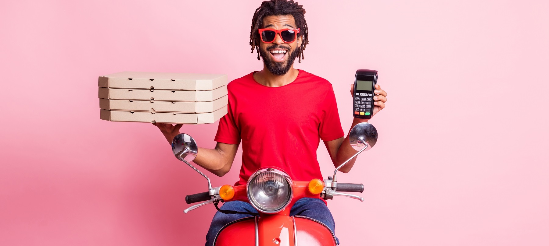 Portrait of handsome cheery guy riding moped delivering pizza holding in hand terminal wireless pay isolated over pink color background.