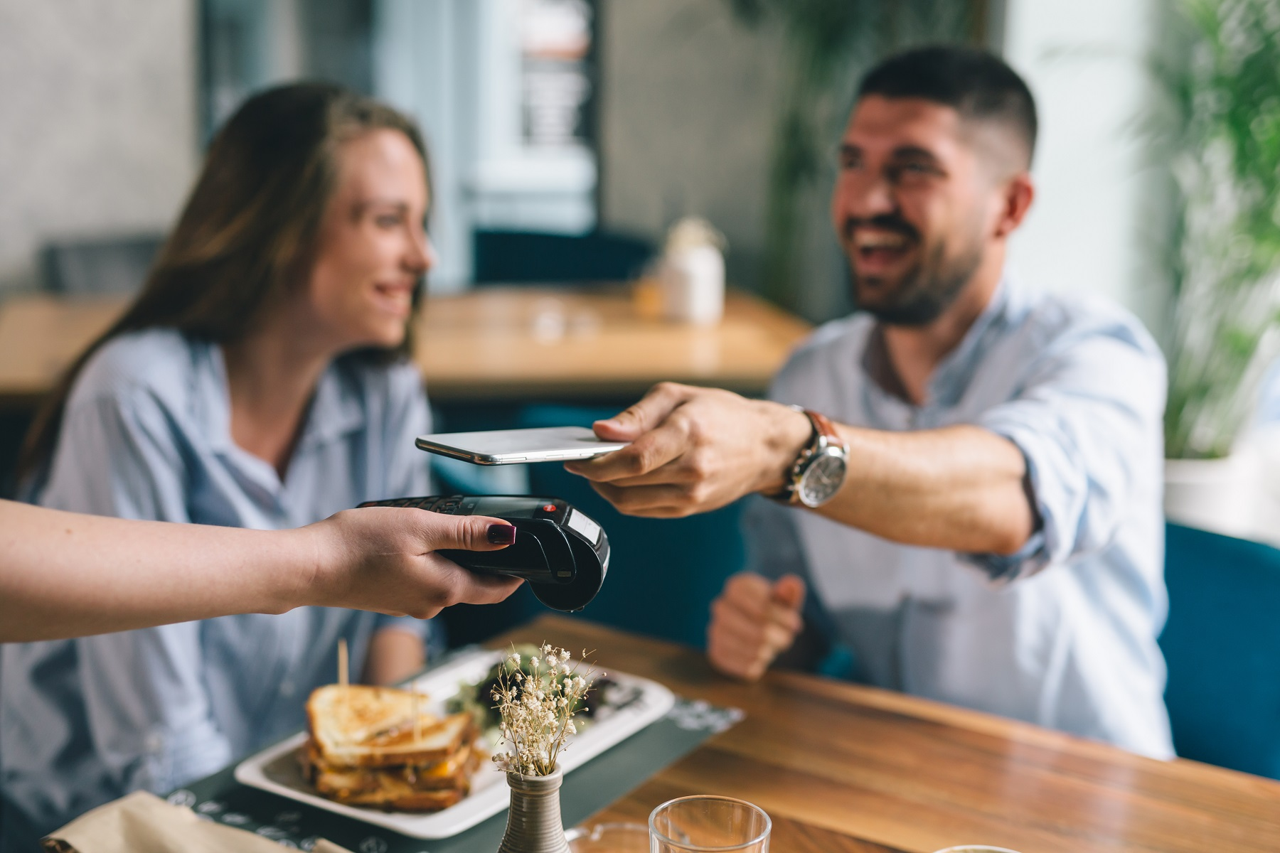 man paying contactless with mobile phone in restaurant